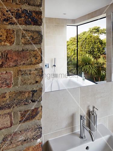 auskragendes fenster spiegelt sich im badezimmer mit backsteinwand bild kaufen living4media. Black Bedroom Furniture Sets. Home Design Ideas