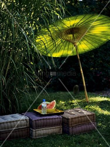 melonenschnitze auf kissen im freien mit gr nem sonnenschirm bild kaufen living4media. Black Bedroom Furniture Sets. Home Design Ideas