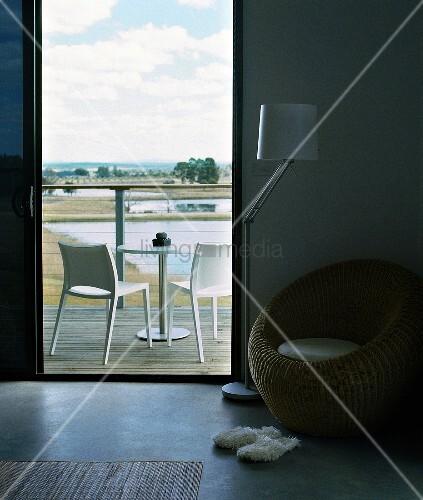 runder korbstuhl in hotelzimmer mit puristischer holzterrasse und blick in die weite landschaft. Black Bedroom Furniture Sets. Home Design Ideas