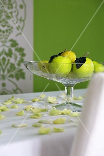 glas obstschale mit gr nen pfel auf wei e tischdecke mit gelb gr nen rosenbl tter bild kaufen. Black Bedroom Furniture Sets. Home Design Ideas