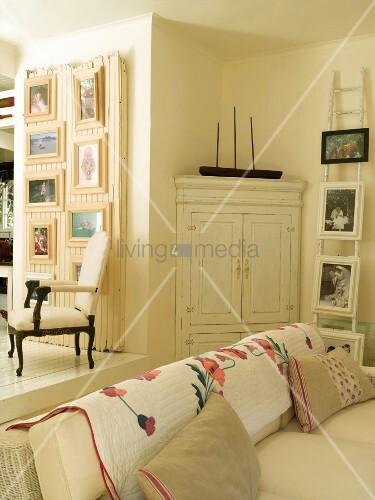 cremefarbenes wohnzimmer im vintage look mit gerahmten bildern an holzleiter und altem. Black Bedroom Furniture Sets. Home Design Ideas