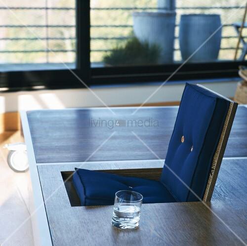 designertisch mit wasserglas neben integriertem klappsitz. Black Bedroom Furniture Sets. Home Design Ideas