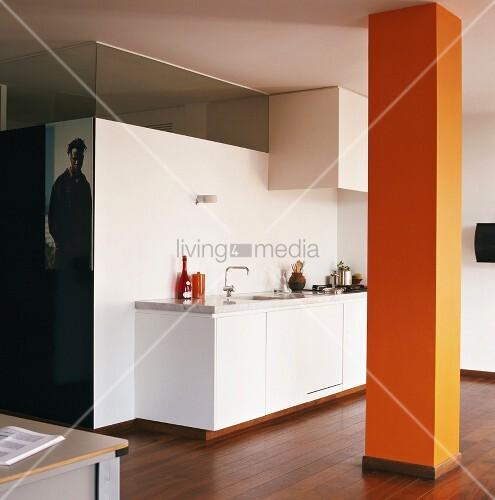 offener raum mit weisser k chenzeile und orangefarbener st tze bild kaufen living4media. Black Bedroom Furniture Sets. Home Design Ideas