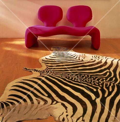 eine rote couch mit lehnen und zebra teppich bild kaufen living4media. Black Bedroom Furniture Sets. Home Design Ideas