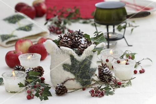 winterliche tischdeko mit kerzen zapfen zier pfel und filz bild kaufen living4media. Black Bedroom Furniture Sets. Home Design Ideas