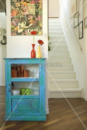 blauer vitrinenschrank und weisse holztreppe bild kaufen living4media. Black Bedroom Furniture Sets. Home Design Ideas