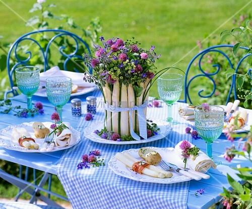 Gedeckter Tisch mit Spargelgericht und Kräuterdeko im Freien ...