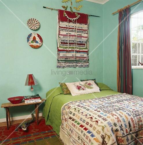 doppelbett mit bunter tagesdecke unter wandteppich bild kaufen living4media. Black Bedroom Furniture Sets. Home Design Ideas
