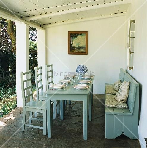Gedeckter holztisch und sitzbank unter berdachte terrasse bild kaufen living4media - Holztisch terrasse ...
