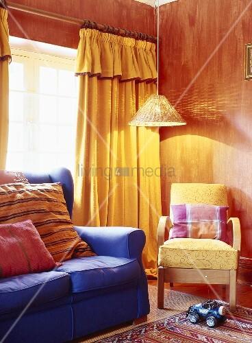 blaues sofa und gelber sessel unter leuchtende h ngelampe im wohnzimmer mit roten w nden und. Black Bedroom Furniture Sets. Home Design Ideas