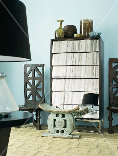 holzkommode mit verspiegelten schubladen zwischen zwei antiken holzst hlen bild kaufen. Black Bedroom Furniture Sets. Home Design Ideas
