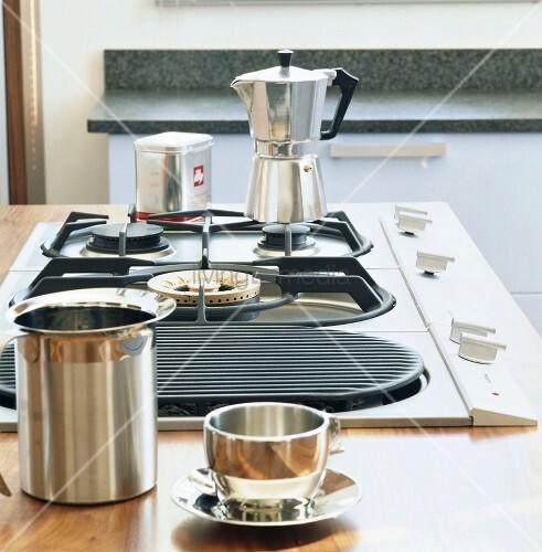 ein kaffeekocher auf dem gasherd im vordergrund eine. Black Bedroom Furniture Sets. Home Design Ideas