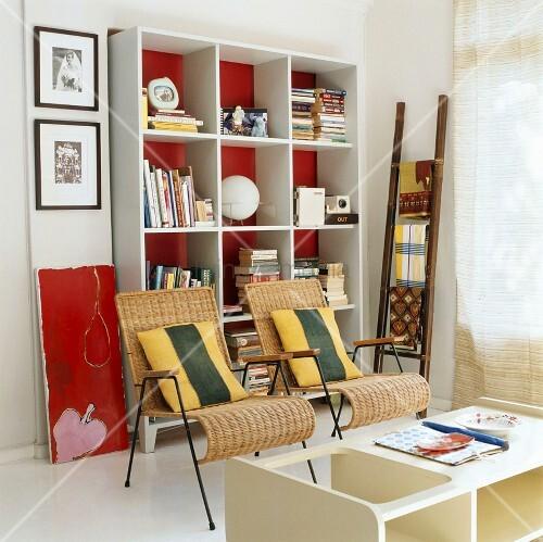 zwei schlanke rattanst hle vor einem weissen b cherregal mit roter r ckwand bild kaufen. Black Bedroom Furniture Sets. Home Design Ideas