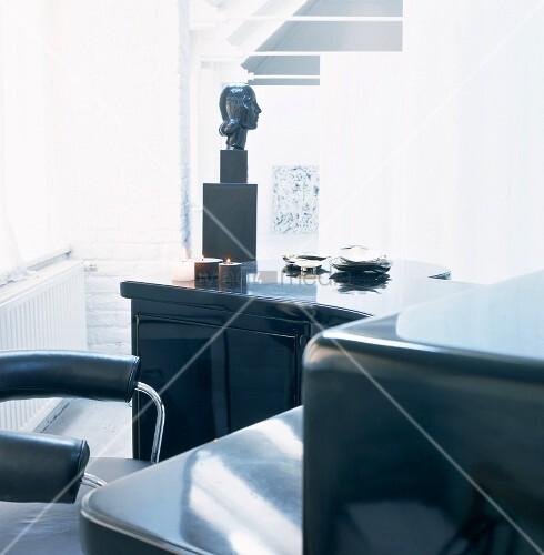 ein schwarzer schreibtisch und brennende kerzen im hellen. Black Bedroom Furniture Sets. Home Design Ideas