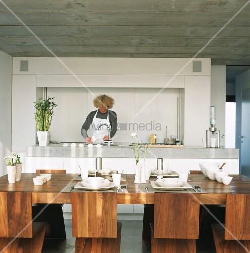 frau bereitet essen in offener k che zu gedeckter tisch im vordergrund bild kaufen living4media. Black Bedroom Furniture Sets. Home Design Ideas