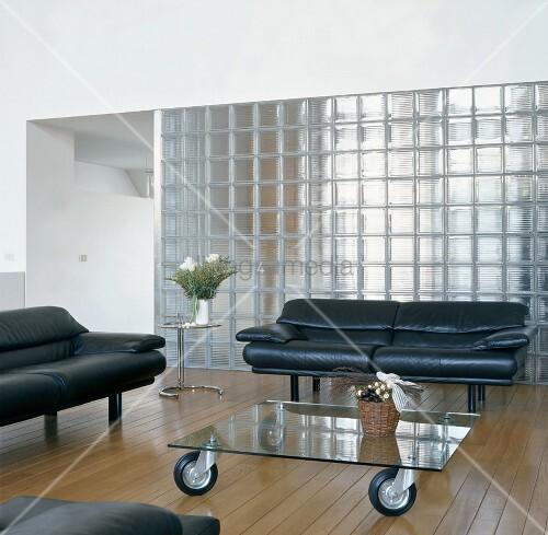 wohnzimmer mit sofas und glastisch auf rollen vor glassteinwand bild kaufen living4media. Black Bedroom Furniture Sets. Home Design Ideas