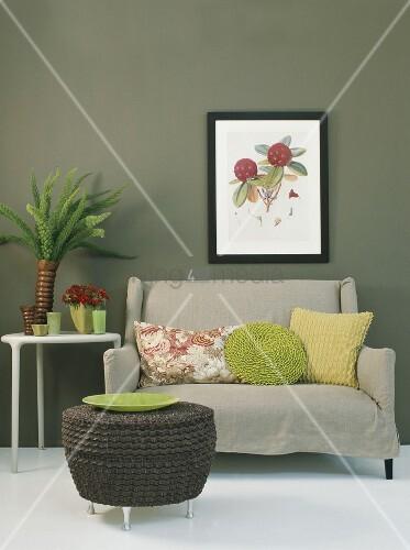 kleines sofa mit zierkissen und rattanhocker unter eingerahmtes bild an grauer wand bild. Black Bedroom Furniture Sets. Home Design Ideas