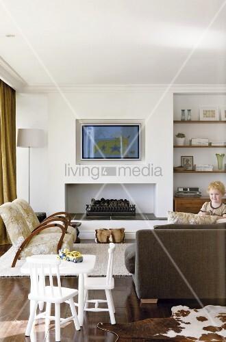 Wohnzimmer mit fernsehger t ber dem offenen kamin und for Wohnzimmer regalwand