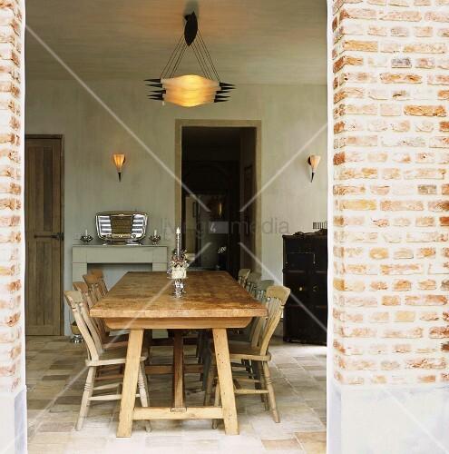 langer massiver esstisch aus holz mit st hlen in rustikal verputztem raum bild kaufen. Black Bedroom Furniture Sets. Home Design Ideas
