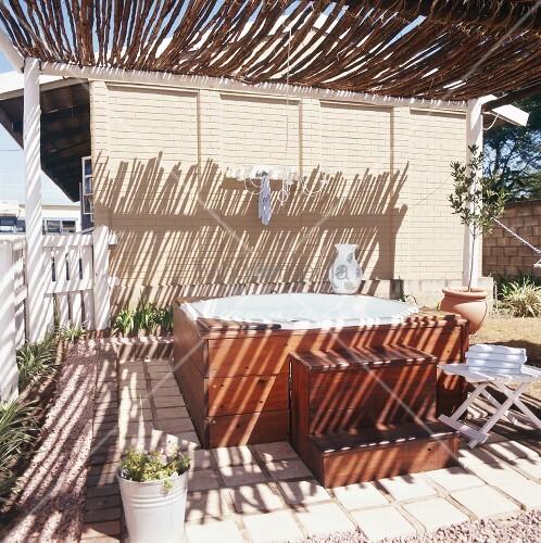 Holzverblendeter whirlpool im garten mit sonnenschutz aus for Whirlpool garten mit bonsai wo kaufen