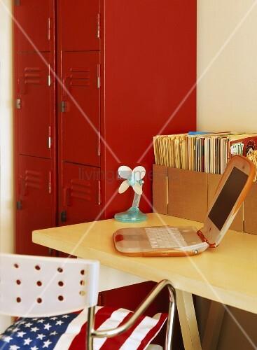 schreibtisch mit laptop neben einem roten spind und stuhl. Black Bedroom Furniture Sets. Home Design Ideas