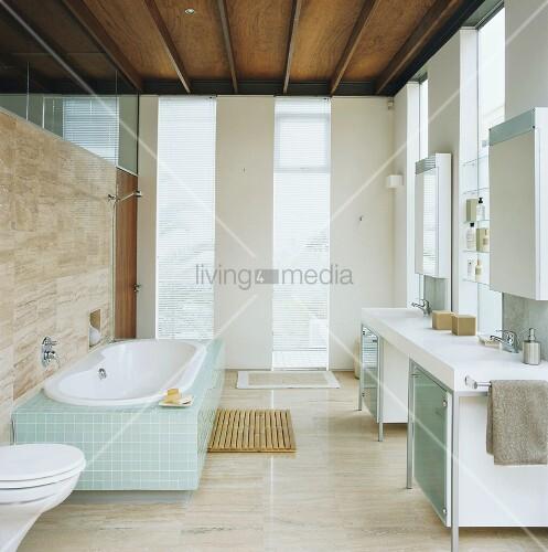 modernes badezimmer mit raumhohen fenstern teilverglaster natursteinwand und holzbalkendecke - Natursteinwand Badezimmer