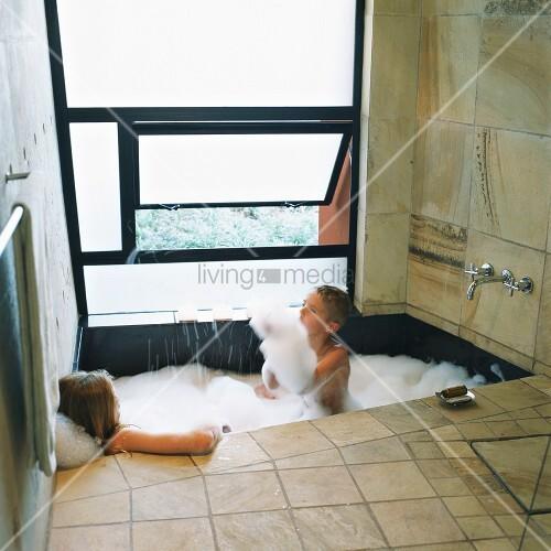 badezimmer aus naturstein mit kippfenster und einer in den boden eingelassenen badewanne bild. Black Bedroom Furniture Sets. Home Design Ideas