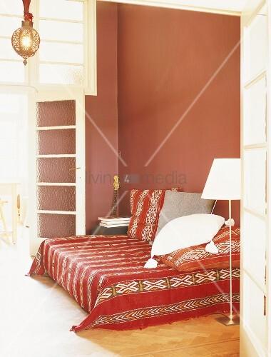 rotes schlafzimmer mit hoher sprossenverglasung und tagesbett im mexikanischen stil bild. Black Bedroom Furniture Sets. Home Design Ideas