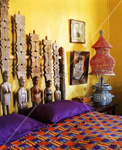 Originelles Kopfteil aus Holzskulpturen im bunten Schlafzimmer im ...