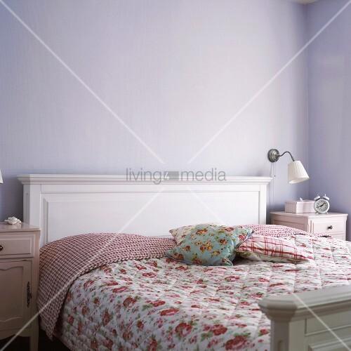 romantische schlafzimmereinrichtung in weiss mit blumenbettw sche vor einer fliederfarbenen wand. Black Bedroom Furniture Sets. Home Design Ideas