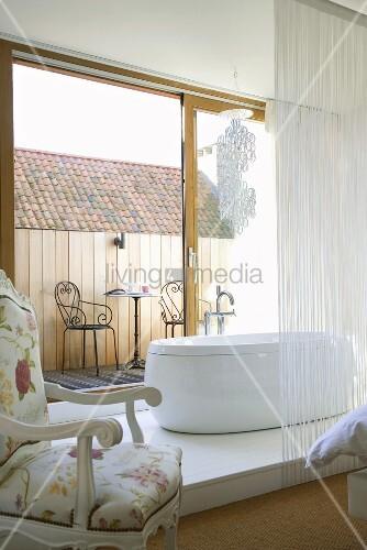 moderne freistehende badewanne auf einem holzpodest vor der ge ffneten balkont r im. Black Bedroom Furniture Sets. Home Design Ideas