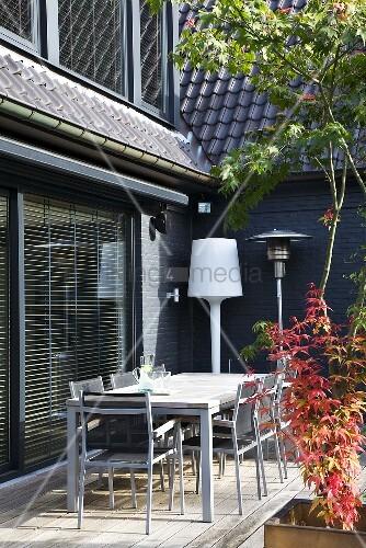 hausecke mit terrassenplatz m bliert mit tisch st hlen und einer stehlampe bild kaufen. Black Bedroom Furniture Sets. Home Design Ideas