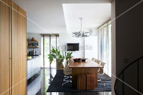 blick in ein esszimmer mit holztisch und st hlen im designerstil schwarzer gl nzender. Black Bedroom Furniture Sets. Home Design Ideas