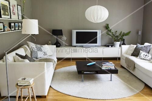Wohnraum mit weisser sofagarnitur und schwarzem couchtisch for Grauer couchtisch