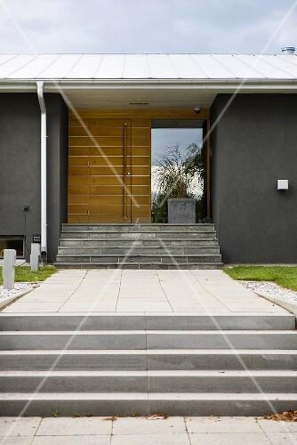 eingangsbereich vor grauem neubau haus mit betonstufen und. Black Bedroom Furniture Sets. Home Design Ideas