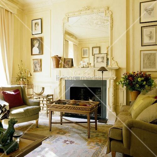 couchtisch und sofagarnitur vor kamin mit verziertem spiegel auf sims im eleganten wohnraum. Black Bedroom Furniture Sets. Home Design Ideas