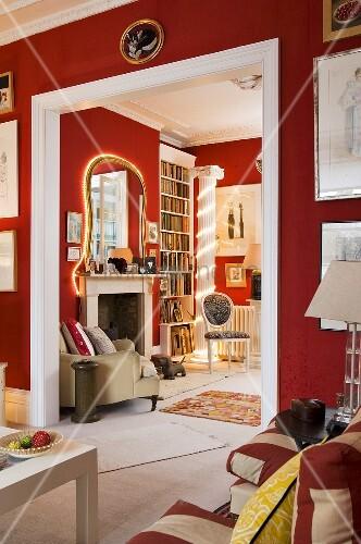 rote w nde im wohnraum mit weissem durchgang und blick auf beleuchteten spiegel und kamin bild. Black Bedroom Furniture Sets. Home Design Ideas