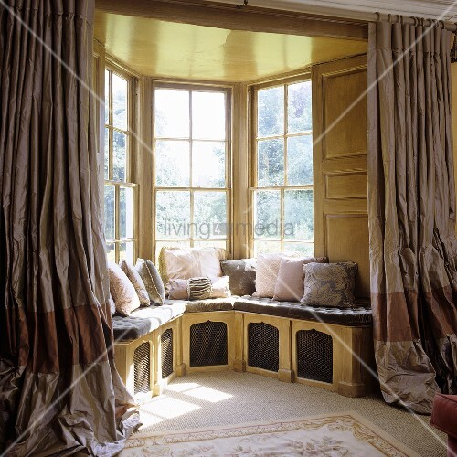 Open Curtains In Front Of A Bay Window With A View And A