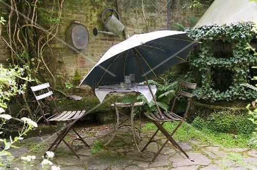 alter gartentisch mit st hlen und sonnenschirm auf natursteinterrasse im hinterhof bild kaufen. Black Bedroom Furniture Sets. Home Design Ideas
