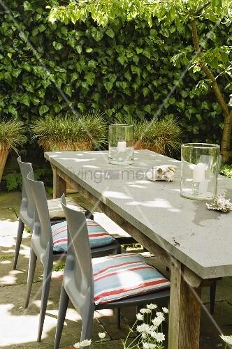 Schlichter holztisch mit grauen plastikst hlen und kissen - Holztisch terrasse ...