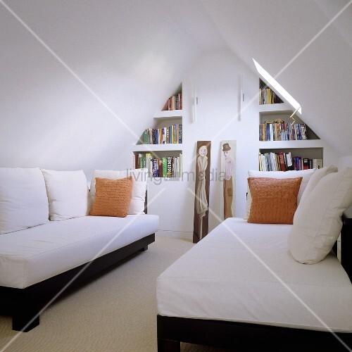 minimalistischer dachraum mit einzelliegen unter dachschr ge und einbauregal bild kaufen. Black Bedroom Furniture Sets. Home Design Ideas