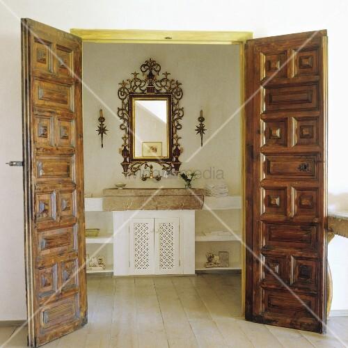 offenstehende holzt ren mit schnitzereien und blick auf steinbecken mit spiegel im goldrahmen. Black Bedroom Furniture Sets. Home Design Ideas