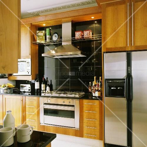 k chenschr nke mit holzfront und integriertem herd mit dunstabzug vor schwarzen wandfliesen. Black Bedroom Furniture Sets. Home Design Ideas