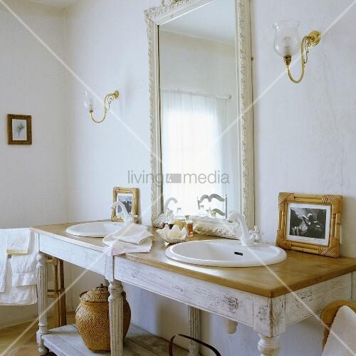 schlichter waschtisch mit zwei becken und weissgerahmter spiegel mit wandbeleuchtung im. Black Bedroom Furniture Sets. Home Design Ideas