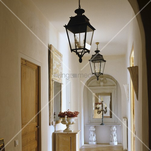 flur im provenzalischem haus mit laternen an der decke und blick durch rundbogen auf antiken. Black Bedroom Furniture Sets. Home Design Ideas