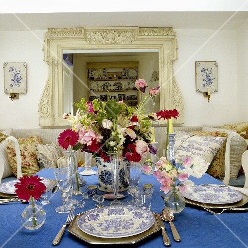 gedeckter tisch mit silberbesteck und blumendeko auf blauer tischdecke bild kaufen living4media. Black Bedroom Furniture Sets. Home Design Ideas