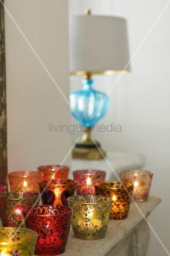 farbige windlichter mit kerzenlicht auf ablage und lampe mit blauem glasfuss auf fensterbank. Black Bedroom Furniture Sets. Home Design Ideas