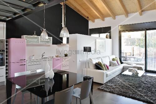 schwarzer tisch im designer wohnraum mit offener k che im fifties stil unter holzbalkendecke. Black Bedroom Furniture Sets. Home Design Ideas