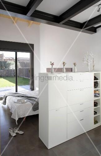 offener schlafraum mit halbhohem schrank als raumteiler vor bett und gartenaussicht bild. Black Bedroom Furniture Sets. Home Design Ideas