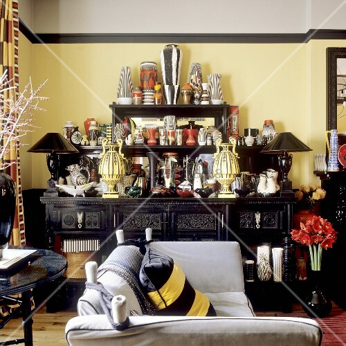 schwarzes buffet mit grosser vasensammlung vor gelber wand bild kaufen living4media. Black Bedroom Furniture Sets. Home Design Ideas